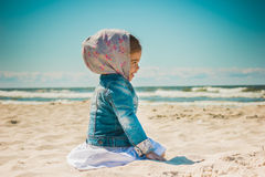 Menina que senta-se na areia na praia Foto de Stock Royalty Free