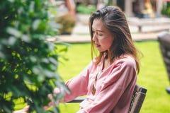 A menina que senta-se na cadeira é distraída fotografia de stock royalty free