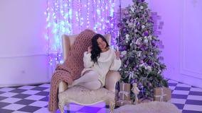 Menina que senta-se na cadeira com champanhe perto da árvore vídeos de arquivo