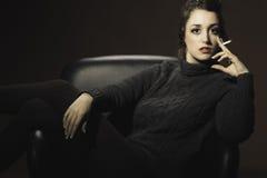 Menina que senta-se na cadeira com cigarros Imagens de Stock Royalty Free