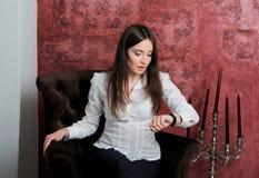 Menina que senta-se na cadeira de veludo e que olha o relógio Foto de Stock