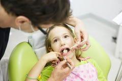 Menina que senta-se na cadeira dental imagens de stock royalty free