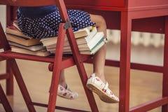 Menina que senta-se na cadeira e nos livros na escola em c Imagem de Stock