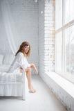 Menina que senta-se na cama Imagens de Stock