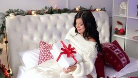 Menina que senta-se na cama com o presente do Natal na manhã video estoque
