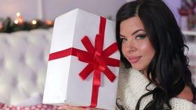 Menina que senta-se na cama com o presente do Natal na manhã vídeos de arquivo