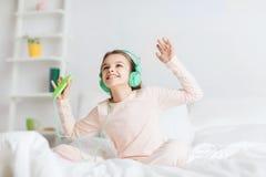 Menina que senta-se na cama com smartphone e fones de ouvido Fotografia de Stock Royalty Free