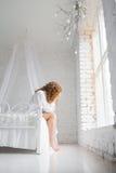 Menina que senta-se na cama jovem mulher virada que senta-se em uma cama apenas fotos de stock