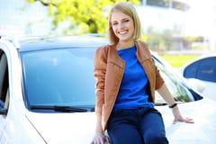Menina que senta-se na capa de um carro Fotos de Stock Royalty Free