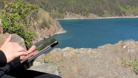Menina que senta-se na costa do Lago Baikal em uma rocha e que usa uma tabuleta video estoque