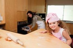 Menina que senta-se na cozinha quando sua matriz pôr biscoitos em t fotos de stock