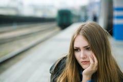 Menina que senta-se na estação de comboio Fotos de Stock