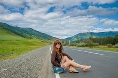 Menina que senta-se na estrada Fotografia de Stock