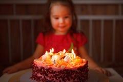 A menina que senta-se na frente de um bolo e faz um desejo a criança antecipa o sopro para fora das velas imagens de stock