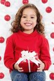 Menina que senta-se na frente de uma árvore de Natal Fotos de Stock Royalty Free