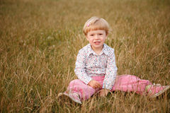 Menina que senta-se na grama Fotografia de Stock Royalty Free