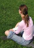 Menina que senta-se na grama Imagens de Stock Royalty Free