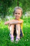Menina que senta-se na grama Fotografia de Stock