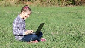 Menina que senta-se na grama e que joga o portátil video estoque