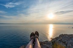 Menina que senta-se na grama na frente do mar no sol de ajuste fotos de stock