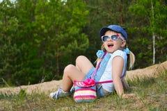 Menina que senta-se na grama no campo e no riso imagens de stock