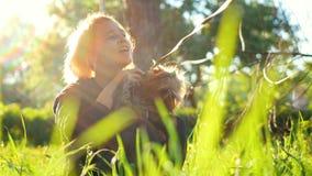 Menina que senta-se na grama no parque, guardando um cão pequeno e afagando o video estoque