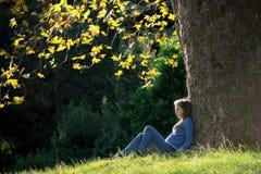 Menina que senta-se na grama sob a árvore de bordo no outono Fotografia de Stock Royalty Free