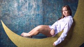 Menina que senta-se na lua Foto de Stock Royalty Free