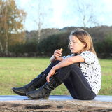Menina que senta-se na madeira Imagens de Stock Royalty Free
