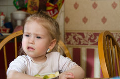 Menina que senta-se na mesa de cozinha Foto de Stock Royalty Free