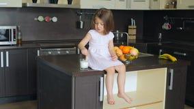 Menina que senta-se na mesa de cozinha vídeos de arquivo