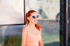 A menina que senta-se na parada do ônibus nos óculos de sol que esperam o ônibus fotos de stock