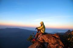 Menina que senta-se na pedra para ver a vista bonita da montanha grande Imagem de Stock Royalty Free