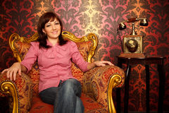 Menina que senta-se na poltrona com um telefone retro imagem de stock
