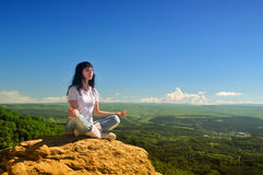 Menina que senta-se na posição dos lótus sobre a montanha Fotografia de Stock