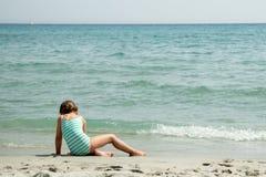 Menina que senta-se na praia perto do oceano imagens de stock royalty free