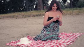 Menina que senta-se na praia, usando o telefone celular e o riso filme