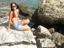 Menina que senta-se na rocha Imagens de Stock Royalty Free