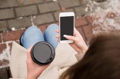 Menina que senta-se na rua com um telefone e um caf? em suas m?os, olhando no telefone, esperando uma chamada, ? inverno fora foto de stock