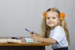 A menina que senta-se na tabela e escreveu em um caderno Fotografia de Stock Royalty Free