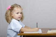 A menina que senta-se na tabela e escreveu em um caderno. Veja o perfil Fotografia de Stock