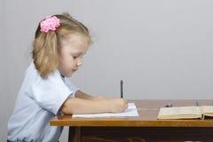 A menina que senta-se na tabela e escreveu em um caderno. Veja o perfil Foto de Stock Royalty Free