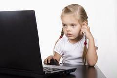A menina que senta-se na tabela e no portátil running Imagens de Stock Royalty Free