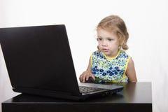 A menina que senta-se na tabela e no portátil running Foto de Stock Royalty Free