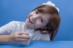 Menina que senta-se na tabela, guardando um vidro do leite imagem de stock