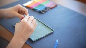 A menina que senta-se na tabela, seleciona figuras diferentes do plasticine do modelo de cor Desenvolvimento da arte que modela d filme