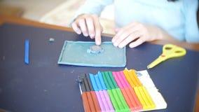 A menina que senta-se na tabela, seleciona figuras diferentes do plasticine do modelo de cor Desenvolvimento da arte que modela d video estoque