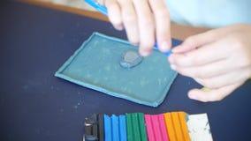A menina que senta-se na tabela, seleciona figuras diferentes do plasticine do modelo de cor Desenvolvimento da arte que modela d vídeos de arquivo