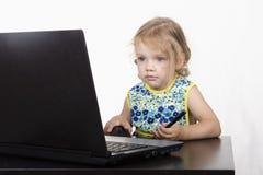 A menina que senta-se na tabela, trabalhando em um portátil, e guardando uma pena Fotos de Stock Royalty Free