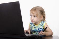 A menina que senta-se na tabela, trabalhando em um portátil, e guardando uma pena Fotos de Stock